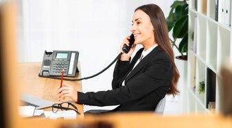 Boczny widok uśmiechnięty młodej kobiety obsiadanie w biurze opowiada na telefonie