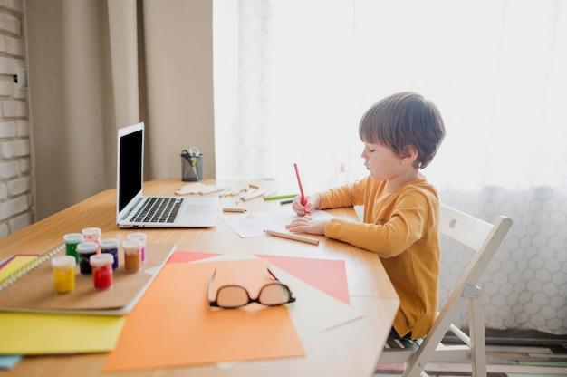Boczny widok uczy się od laptopu dziecko podczas gdy w domu