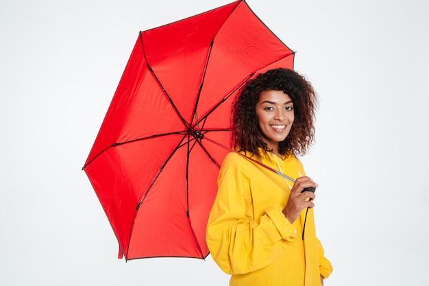 Boczny widok uśmiechnięta afrykańska kobieta w deszczowa pozować