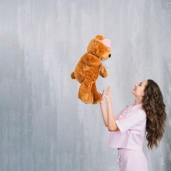 Boczny widok uśmiechnięta młoda kobieta rzuca miękką zabawkę w powietrzu