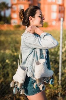 Boczny widok uśmiechnięta młoda kobieta trzyma rolkowej łyżwy na jej ramieniu