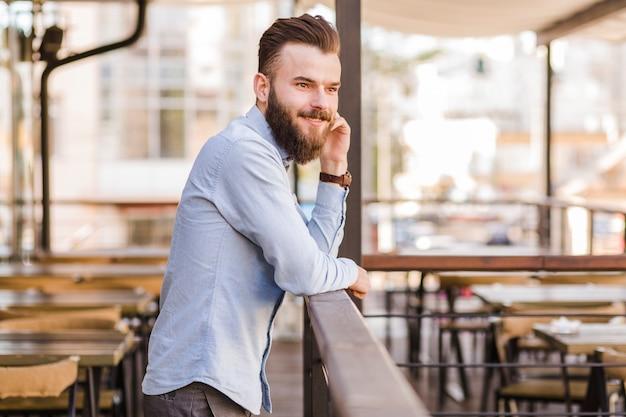 Boczny widok uśmiechnięta młody człowiek pozycja w restauraci