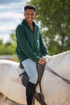 Boczny widok uśmiechniętego młodego amerykanina afrykańskiego pochodzenia męska patrzeje kamera podczas gdy siedzący na plecy biały koń