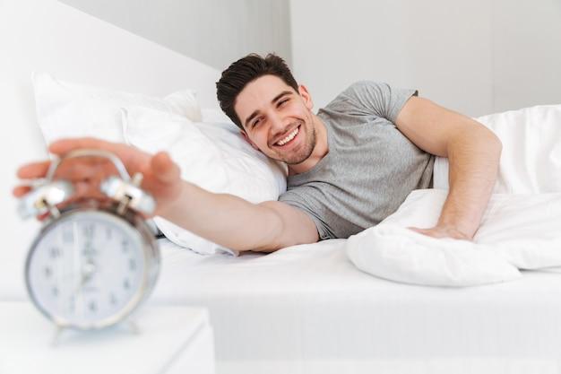 Boczny widok uśmiechnięty brunetka mężczyzna lying on the beach na łóżku