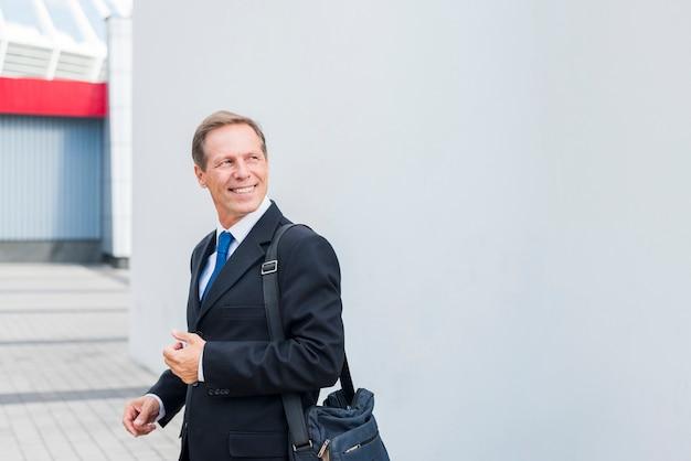 Boczny widok uśmiechnięty dojrzały biznesmen przy outdoors