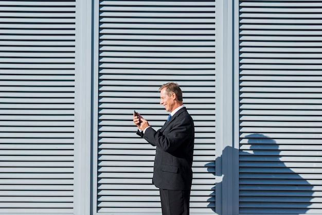 Boczny widok uśmiechnięty dojrzały biznesmen używa telefon komórkowego przy outdoors