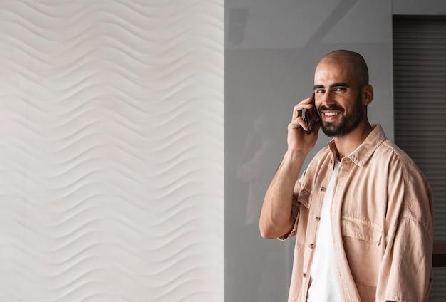 Boczny widok uśmiechnięty mężczyzna rozmawia przez telefon