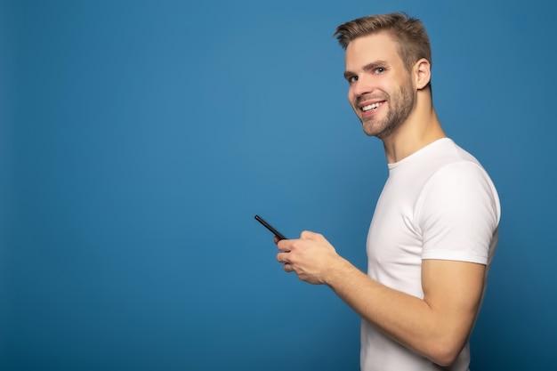 Boczny widok uśmiechnięty młody człowiek używa smartphone odizolowywającego na błękicie