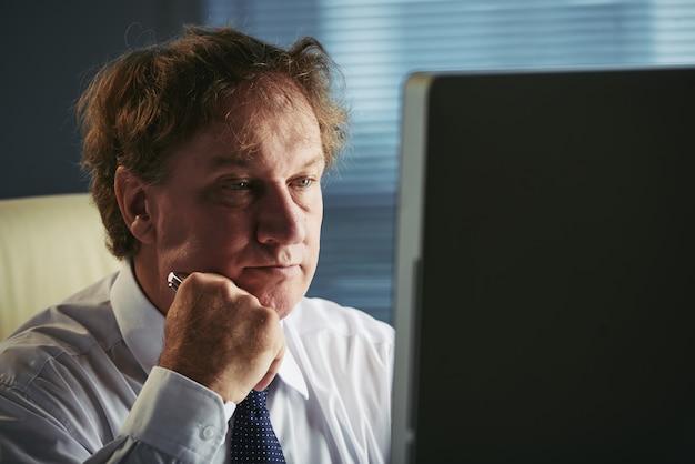 Boczny widok w średnim wieku mężczyzna czyta biznesowych artykuły na sieci przy pracą