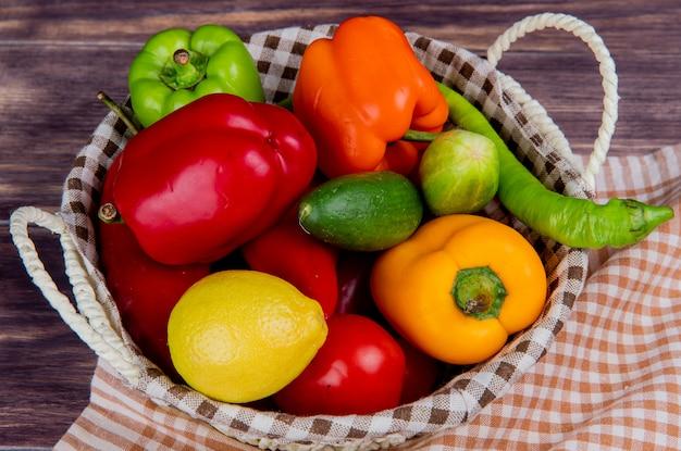 Boczny widok warzywa jako ogórkowy pieprzowy pomidor w koszu na szkockiej kraty płótnie i drewnianym stole