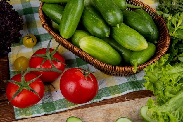 Boczny widok warzywa jako pomidorowi ogórki w koszykowym basilu i sałacie na płótnie i drewnianym stole