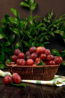 Boczny widok wiązka świezi słodcy winogrona w łozinowym koszu na zielonym liścia stole