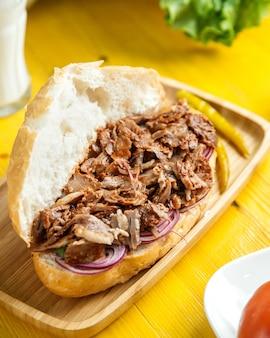 Boczny widok wołowina doner w chlebie z kiszonym zielonym pieprzem na drewnianym półmisku