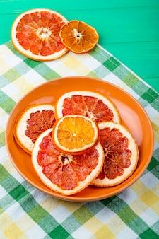 Boczny widok wysuszeni pomarańcze i grapefruitowi plasterki w talerzu na szkocka krata tablecloth na zielonym drewnianym tle