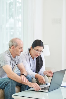 Boczny widok wyszukuje sieć na laptopie z lekarką starszy pacjent