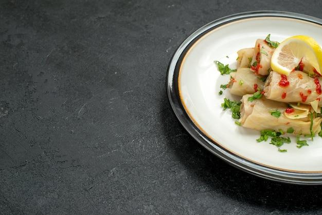 Boczny widok z bliska talerz apetycznego dania gołąbkowanej kapusty z ziołami cytryną i sosem na białym talerzu po prawej stronie czarnego stołu