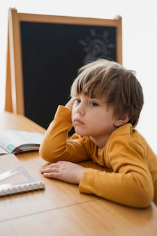 Boczny widok zanudzający dziecko przy biurkiem z notatnikiem i blackboard