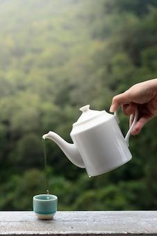 Boczny widok żeńska dolewanie herbata przy herbacianą rośliną.