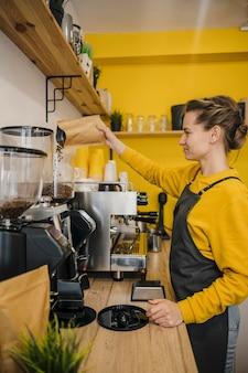 Boczny widok żeńskiego barista mielenia kawa
