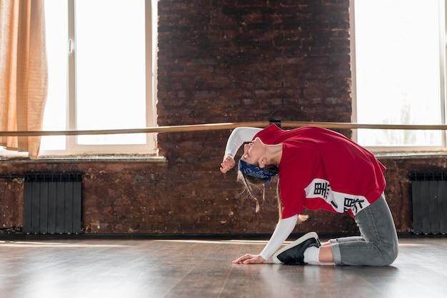 Boczny widok żeńskiego tancerza robi ćwiczeniu w tana studiu