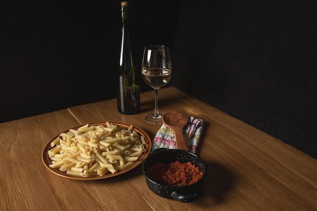 Bodegon z makaronu z sosem bolognese i tartym serem i kieliszkiem wina towarzyszącego.