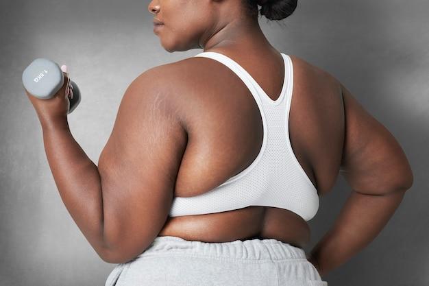 Body positivity krągła kobieta sportowa z hantlami
