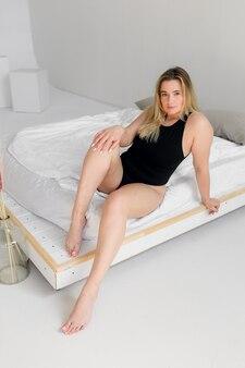 Body pozytywne kobieta w czarnej bieliźnie pozuje na nowoczesnym białym wnętrzu