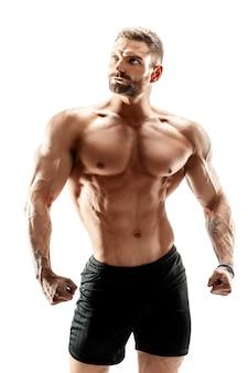 Bodybuilder pokazuje jego mięśnie odizolowywających na bielu