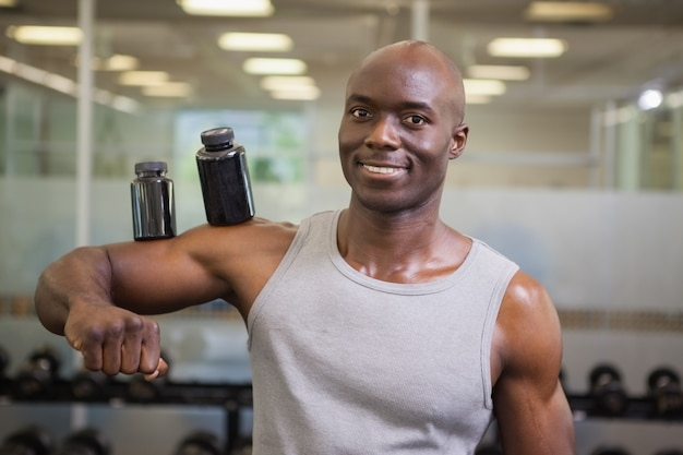 Bodybuilder trzyma butelki z dodatkami na bicepsie