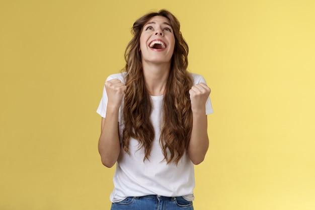 Bóg w końcu tak. z ulgą wdzięczna szczęśliwa szczęśliwa dziewczyna spojrzeć w górę dzięki bogu pięść pompa świętowanie sukces zwycięstwo triumfujący zacisk ramiona wdzięczny zachwycony szczęście szansa stoisko żółte tło.