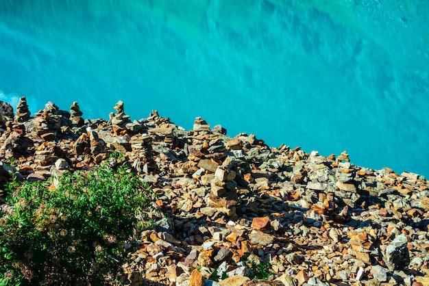 Bogata roślinność na skalistym klifie nad lazurowym jeziorem.