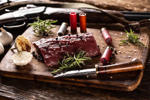 Bogata w składniki odżywcze surowa dziczyzna z jelenia przygotowana do procesu gotowania na rustykalnym drewnianym biurku z pieczonym czosnkiem, rozmarynem i akcesoriami myśliwskimi, takimi jak strzelba i amunicja