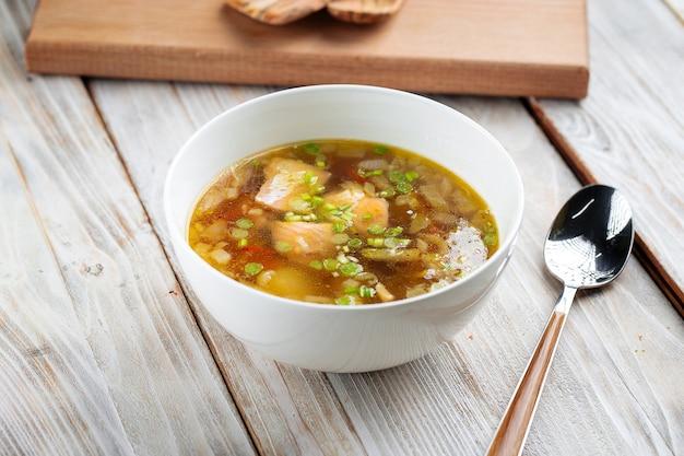 Bogata zupa rybna w białej misce na drewnianym stole