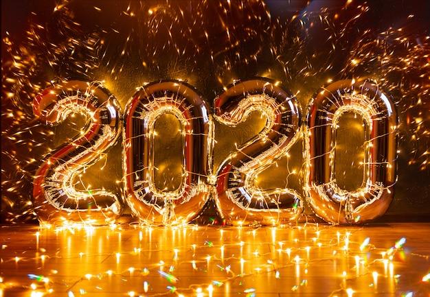Bogate nadmuchiwane postacie 2020 na ciemnej ścianie, owinięte w świąteczne lampki z pięknymi akcentami i miejscem na tekst