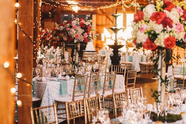 Bogate stoły obiadowe pokryte niebieskimi ubraniami i lśniącym szkłem