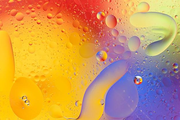 Bogate wielobarwne tło kropli oleju na powierzchni wody z bąbelkami i rozmazami, koncepcja tekstury sztuki