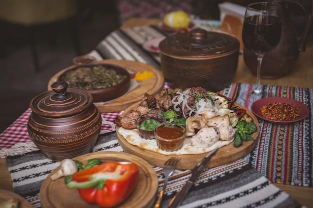 Bogato zastawione dania kuchni gruzińskiej, dużo pysznego jedzenia, wina, owoców i pieczonego mięsa