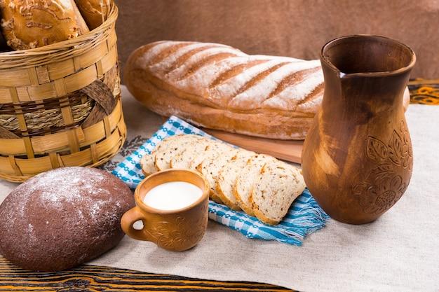 Bogato zdobiony drewniany dzbanek, mały kubek mleka i świeżo upieczony chleb jako cały bochenek i kromki obok kosza na stole