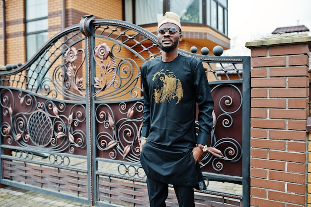 Bogaty afrykański mężczyzna w stylowych tradycyjnych strojach i kapeluszu stanowił tło swojej rezydencji.