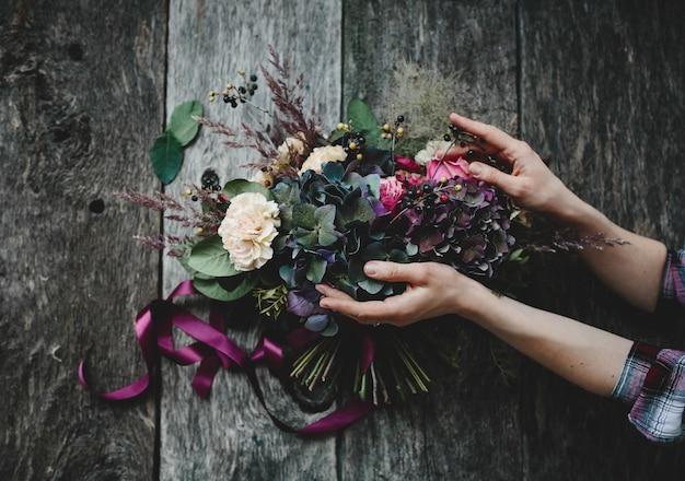 Bogaty bukiet ciemnych kwiatów i białych róż leży na drewnianym stole