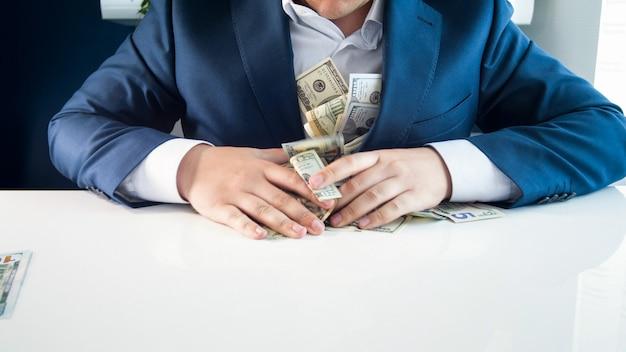 Bogaty chciwy biznesmen napełniający kieszenie pieniędzmi.