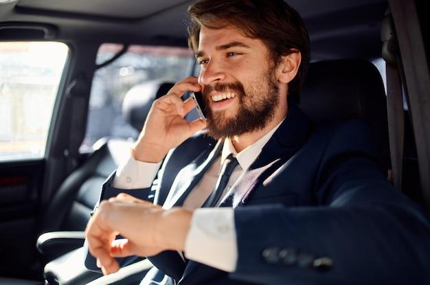 Bogaty człowiek sukcesu w garniturze rozmawia przez telefon podczas prowadzenia samochodu osobowego