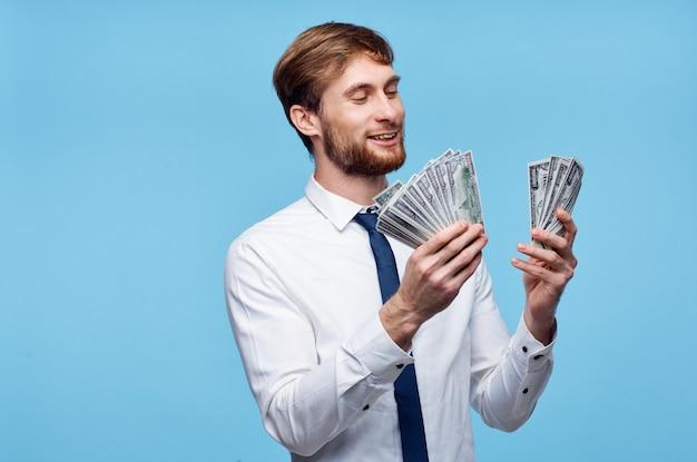 Bogaty człowiek w garniturze z pieniędzmi w ręce emocje niebieskie tło