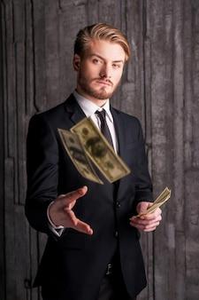 Bogaty i odnoszący sukcesy. przystojny młody mężczyzna w formalwear rzuca pieniądze i patrzy na kamerę