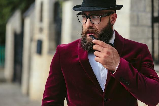 Bogaty mężczyzna z brodą pali elektroniczny papieros