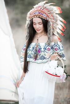 Boho artystyczna dziewczyna ubrana w indyjską sukienkę maxi i biżuterię w jesiennym polu
