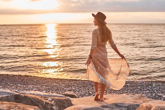 Boho kobieta w długiej sukni i filcowym kapeluszu