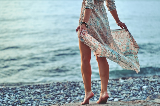 Boho kobieta z falującą sukienką stojącą na brzegu morza o zachodzie słońca