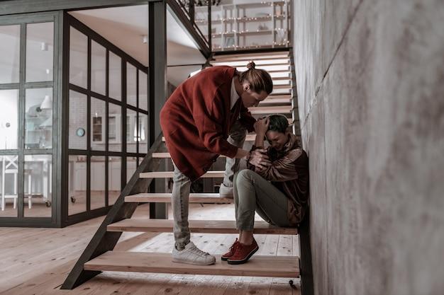 Boi się chłopaka. dziewczyna siedząca na schodach boi się swojego rozzłoszczonego emocjonalnego chłopaka