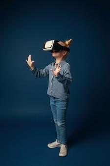 Boi się robić krok. mała dziewczynka lub dziecko w dżinsach i koszuli z okularami zestawu słuchawkowego wirtualnej rzeczywistości na białym tle na niebieskim tle studio. koncepcja najnowocześniejszej technologii, gier wideo, innowacji.
